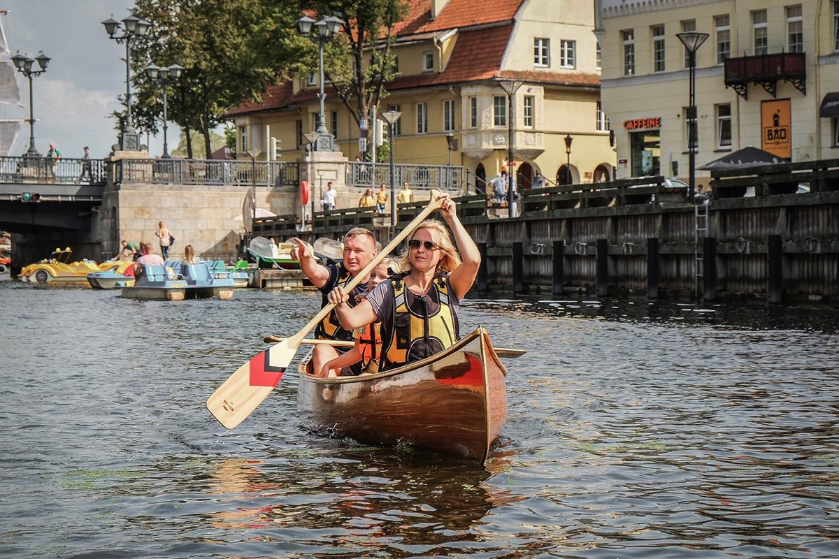 Family paddling canoe in Klaipeda city center